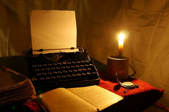 candle, old typewriter and old book